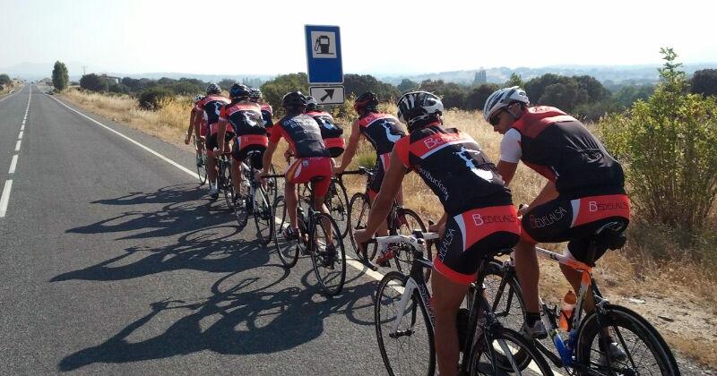 Ciclistas uniformados con la marca del patrocinador por una carretera comarcal