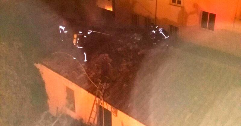 tareas de extincion de lso bomberos desde un tejado aledaño a la casa del fuego