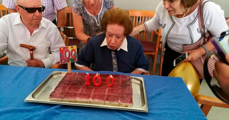 La centenaria soplando las velas de la celebracion