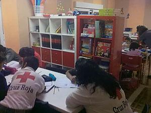 voluntarios de cruz roja trabajan sobre una mesa con escolares