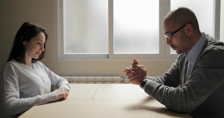 una pareja habla sentados a una mesa