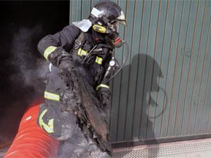 Bombero de Béjar saliendo de la nave donde ardió el vehículo