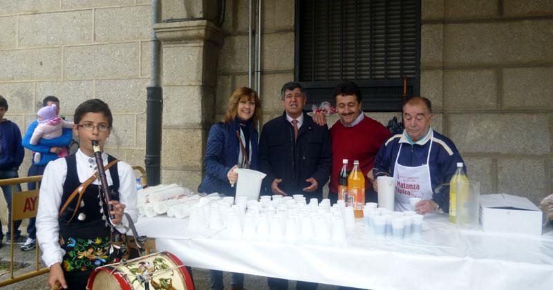 Purificacion Pozo, Alejo Riñones y pedro manuel esteban posan junto a un colaborador repartiendo raciones de comida de la matanza