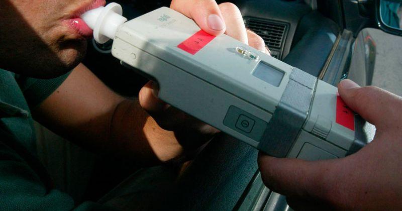 Un agente haciendo a un conductor prueba de alcoholemia