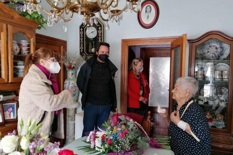 Cuatro personas en el interior de una casa, con un ramo de flores sobre la mesa