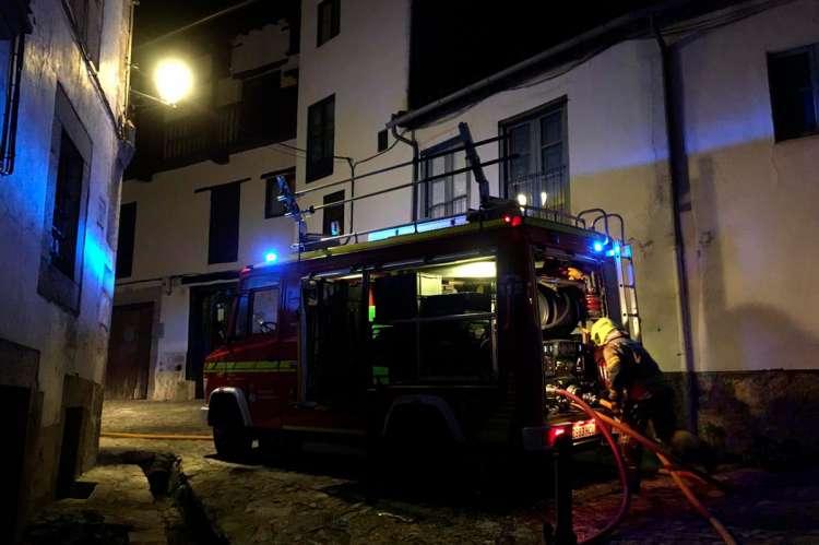 Camión de bomberos y varios bomberos en una calle