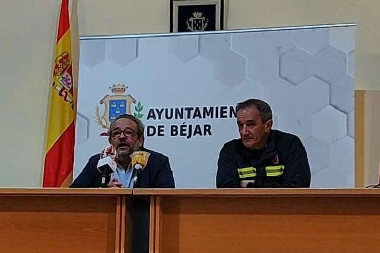 Dos personas sentadas en una mesa con microfonos