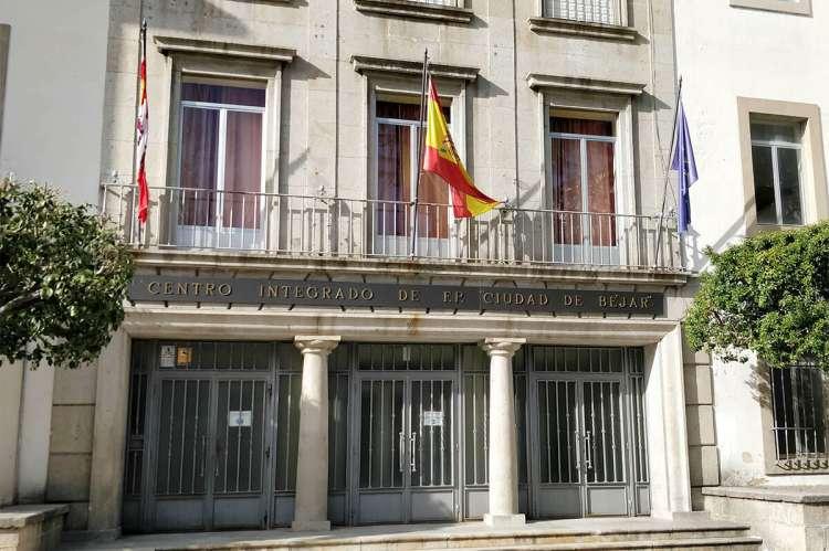 Vista parcial exterior del edificio, con tres puertas principales. Balcón con banderas