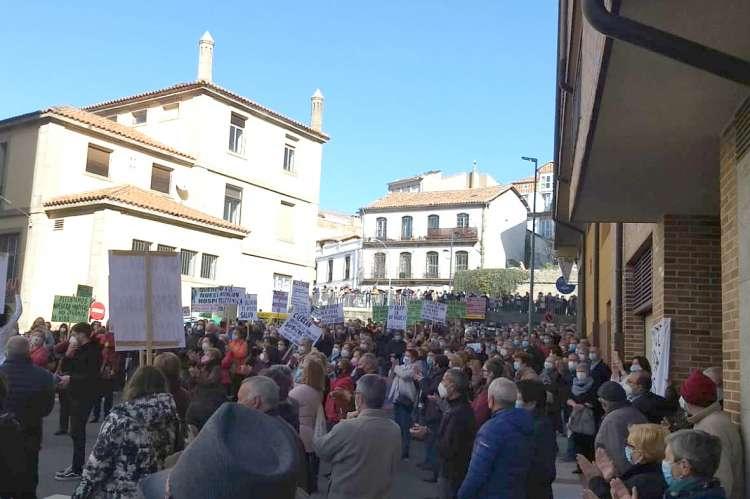 Miles de personas en la calle con pancartas frente al edificio del hospital