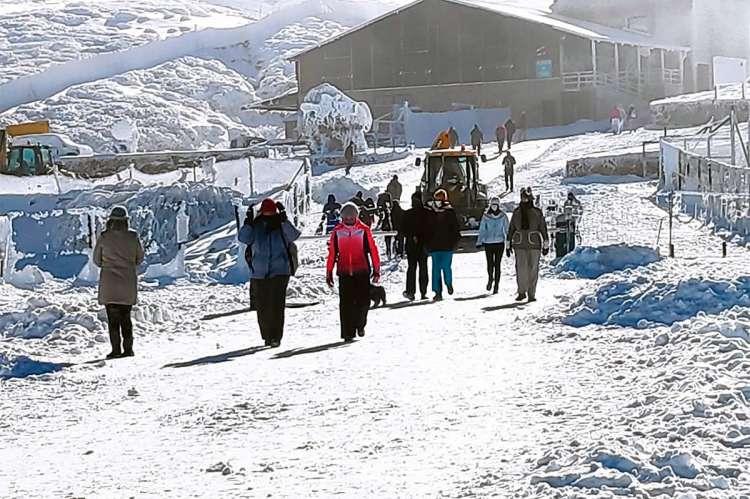 Montaña nevada con edificio al fondo y gente andando