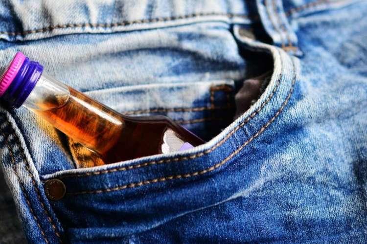 Botella alcohólica dentro del bolsillo de un pantalón vaquero