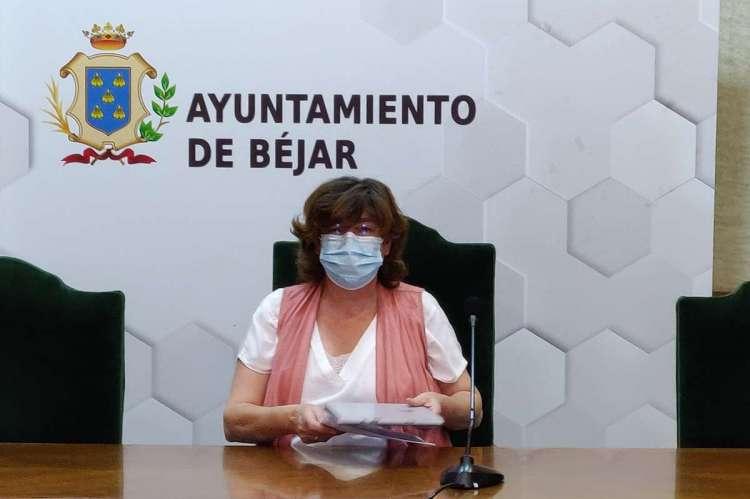 Una mujer sentada en una mesa con papeles en las mano