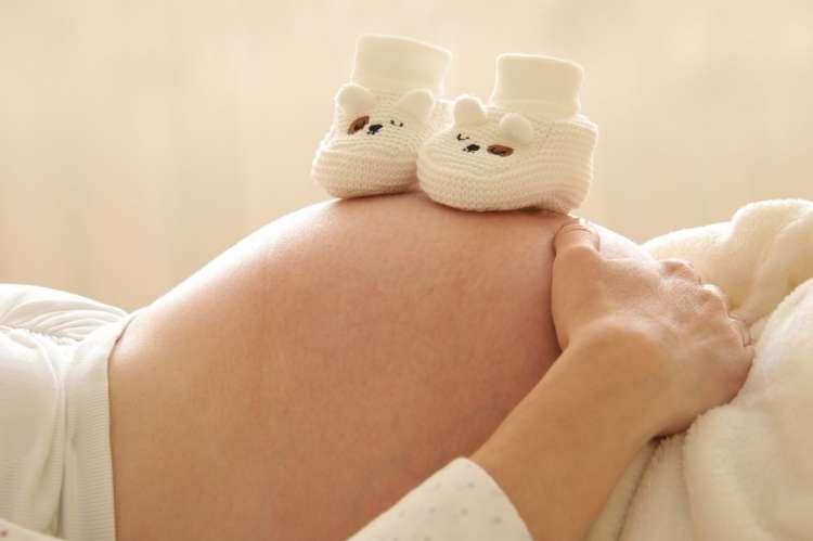 Mujer embarazada tumbada con patucos sobre su barriga