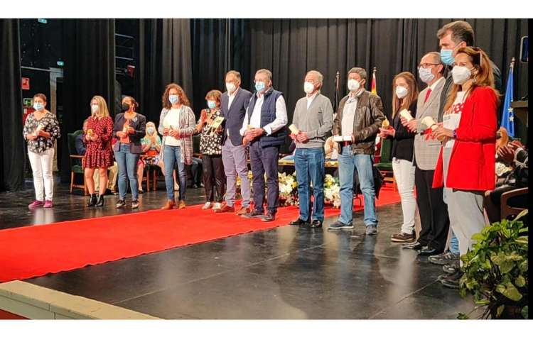 Grupo de personas sobre el escenario del teatro, cubierto parcialmente con alfombra roja