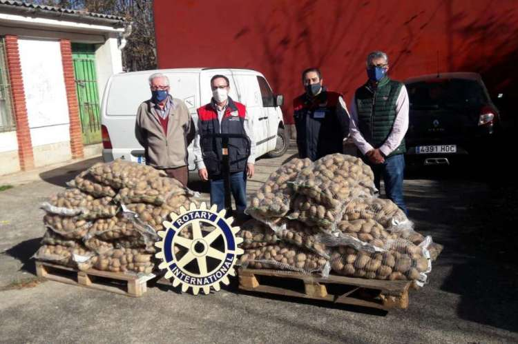 Varias personas con sacos de patatas delante