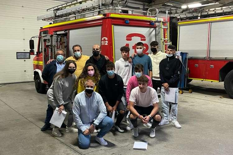 Varias personas con diplomas de la mano. Al fondo varios camiones de bomberos