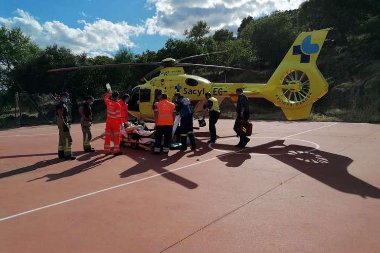 Helicóptero del 112, sanitarios y bomberos durante el traslado del herido