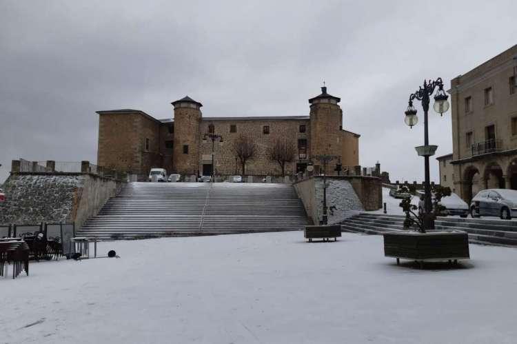 Plaza con palacio ducal al fondo, todo nevado
