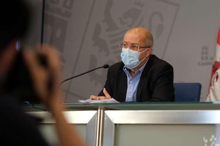 Hombre con mascarilla sentado a una mesa con microfono