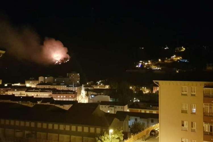 Bloques de edificios y al fondo las llamas del incendio