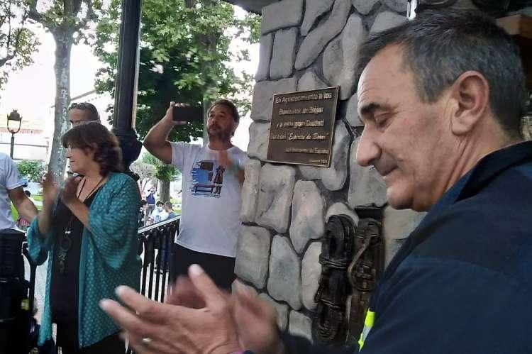Varias personas aplaudiendo con una placa conmemorativa de fondo