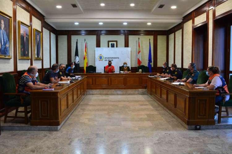 Varias personas sentadas alrededor de una mesa en forma de U
