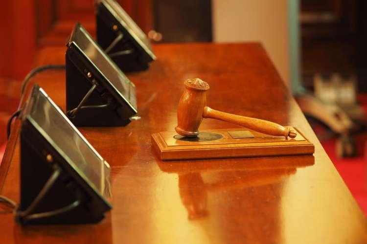 Mesa con mazo de juez y 3 monitores