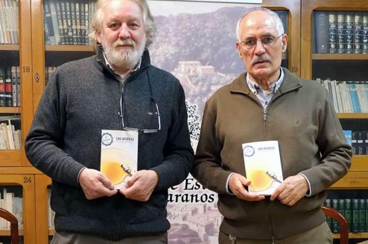 Dos personas sosteniendo un libro entre sus manos