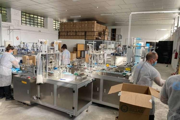 Varios operarios, entre maquinas, fabricando mascarillas