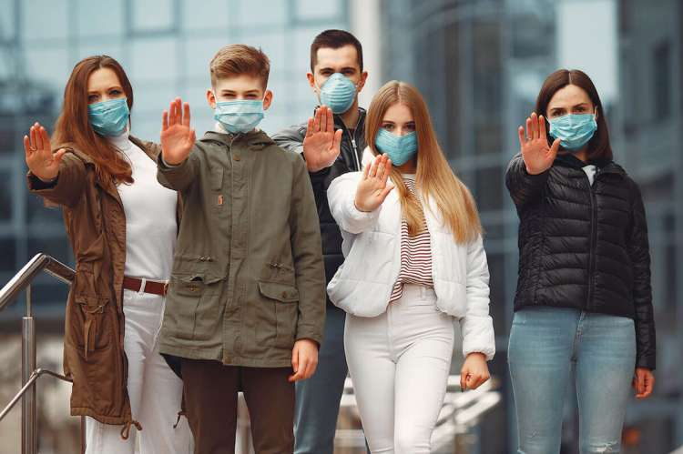 Personas usando mascarillas protectoras muestran señales de alto con las manos