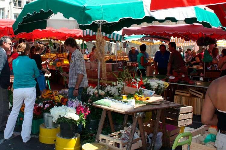 puesto mercadillo flores, fruta con varias personas