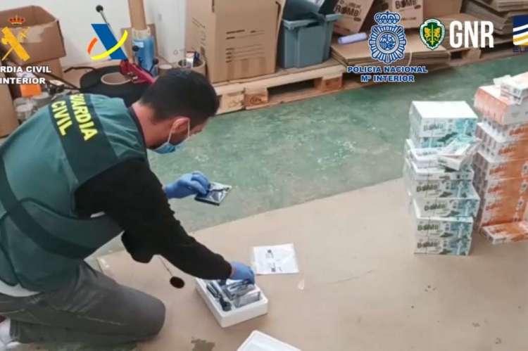 Un agentge examina parte del material incautado en la operacion