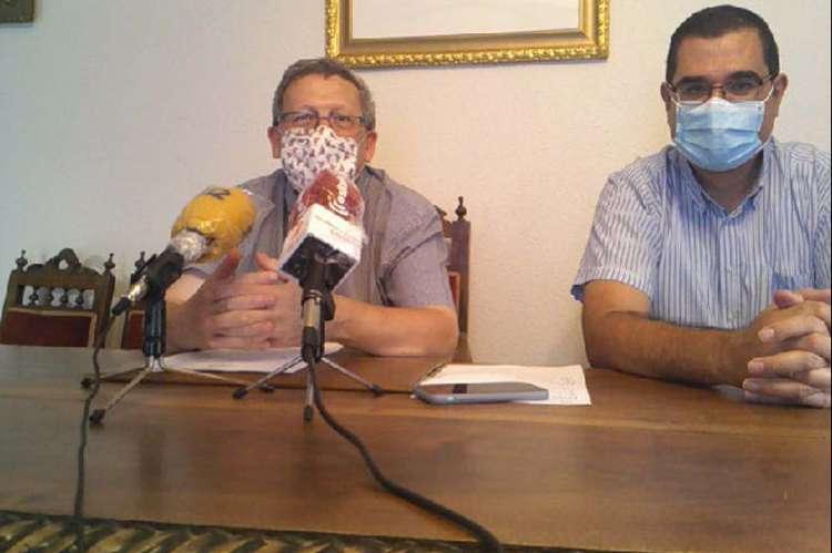 Dos hombres sentados a una mesa con microfonos