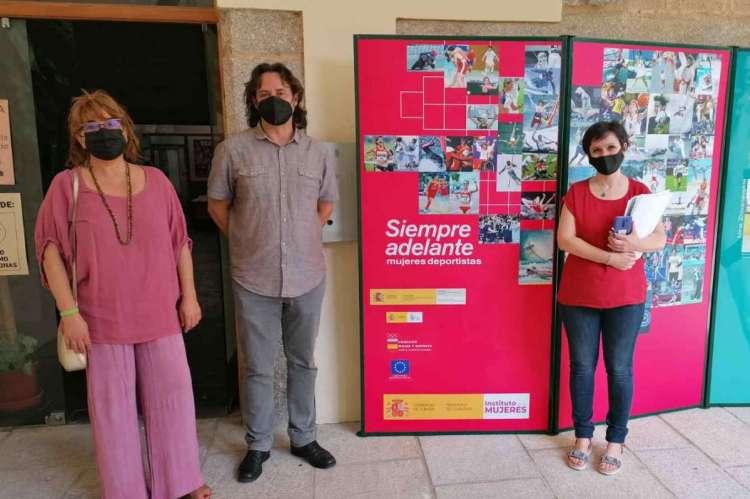 tres personas junto a varios carteles de la exposición