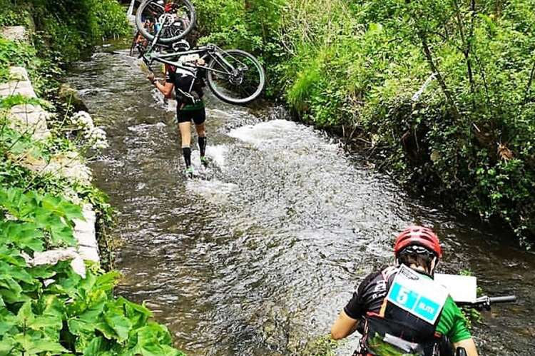Dos raiders con sus bicicletas por un río