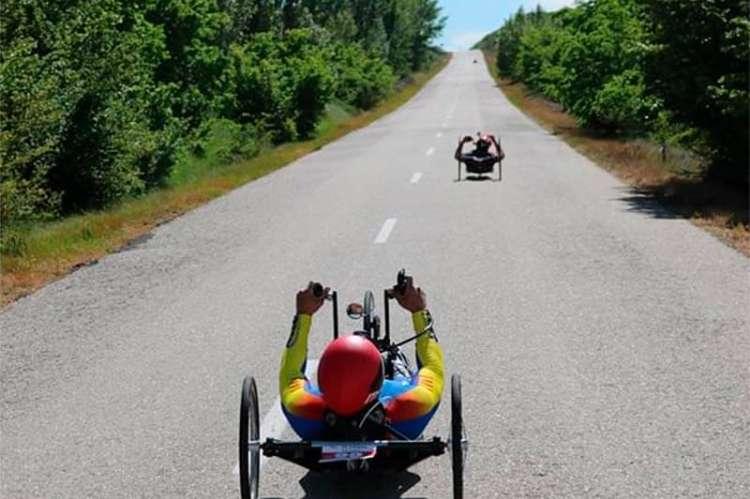 Dos ciclistas en bicicleta adaptada durante la disputa de una carrera