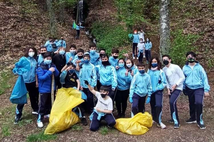 Una veintena de niños con bolsas con la basura recogida, en el bosque