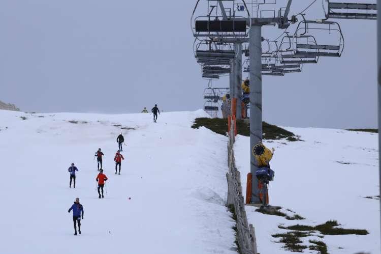 Varios corredores bajando por una pista de nueve junto al telesilla