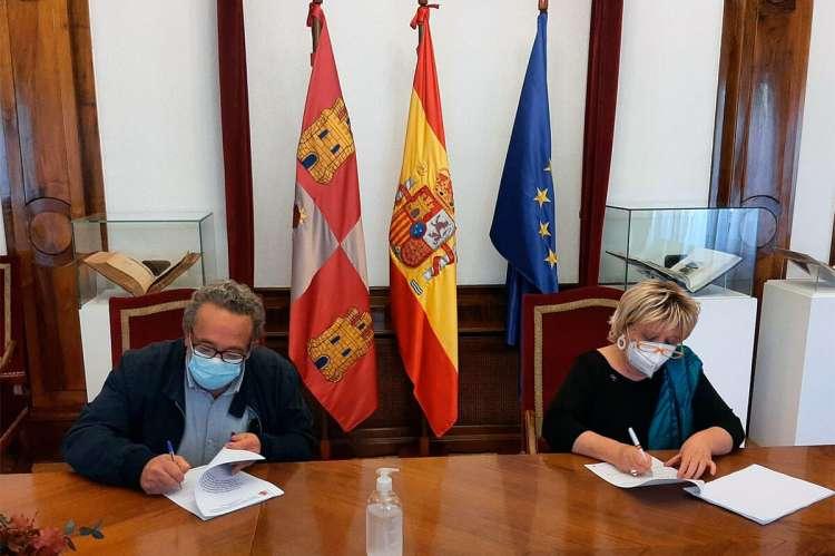 Dos personas firmando un documento sentados en una mesa