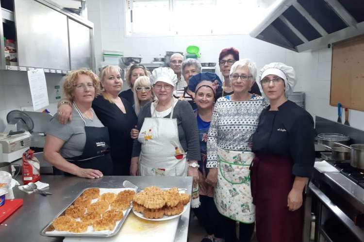 TaVarias personas en una cocina mostrando platos preparados