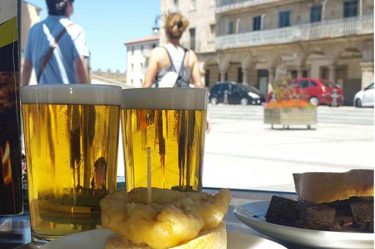 Mesa de la terraza de un bar con cervezas y pinchos