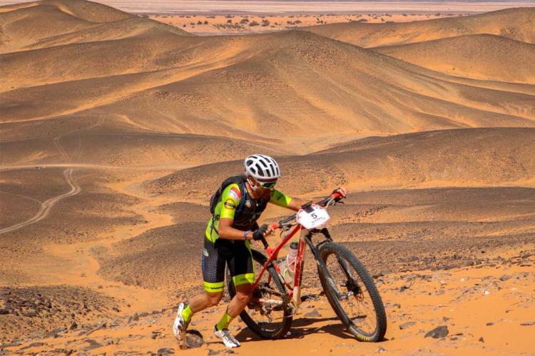 Moisés Dueñas empujando la bicicleta en la Titan Desert
