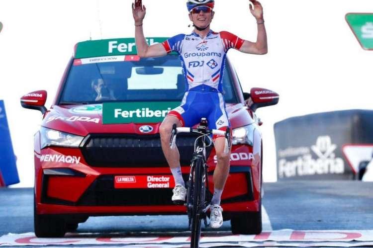 Ciclista con brazos en alto con coche detrás