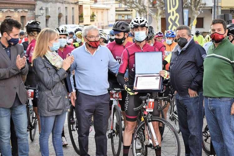 Varias personas junto a un ciclista con placa en las manos