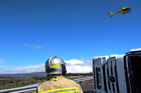 Bombero de Béjar junto al camión accidentado y el helicóptero del Sacyl sobrevolando