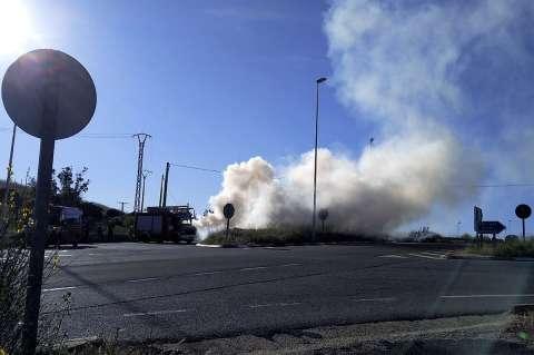Humo blanco saliendo del coche incendiado. Junto al coche varias dotaciones de bomberos