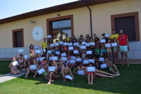 Niños y niñas de los campamentos municipales con su diploma en la piscina de La Cerrallana