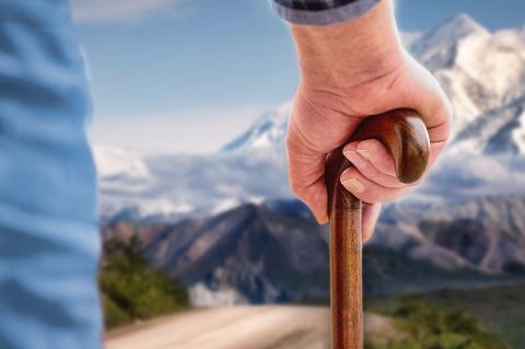 Anciano apoyado en un bastón mira la sierra