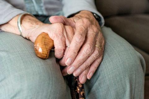 Manos de una persona mayor apoyadas en un bastón