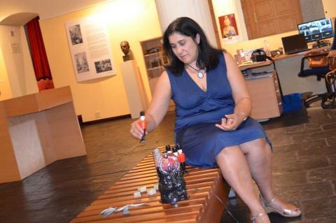 Raquel González sentada en un banco en el museo Valeriano Salas jugando con soldados de madera